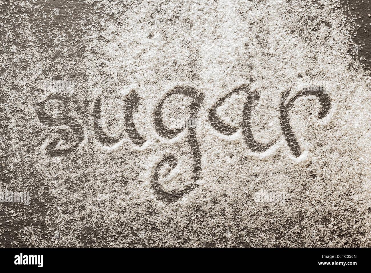 The word sugar written into a pile of white granulated sugar - Stock Image