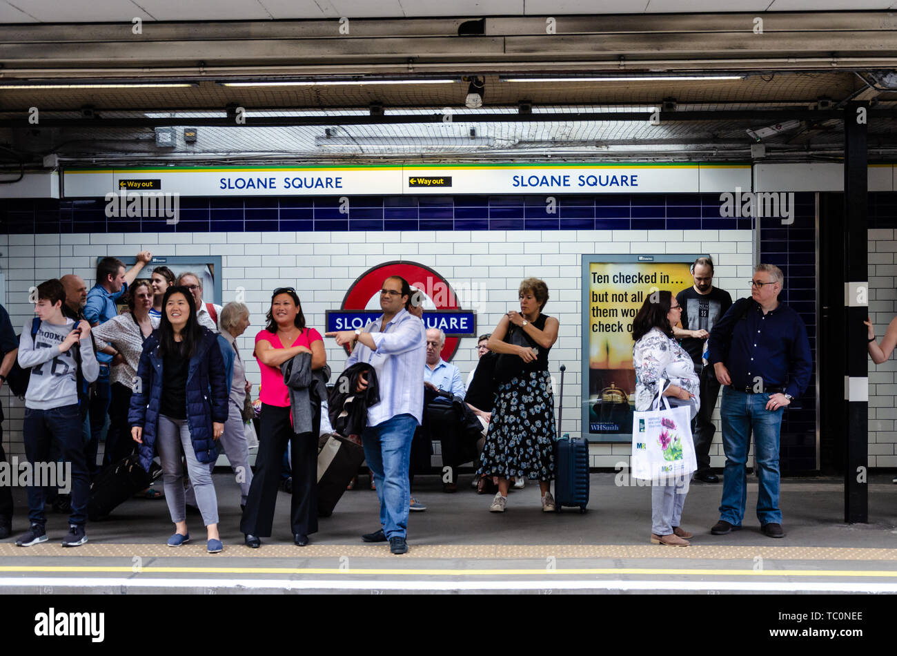 People stand and wait for a train on the platform at Sloane Square London Underground Tube Station - Stock Image