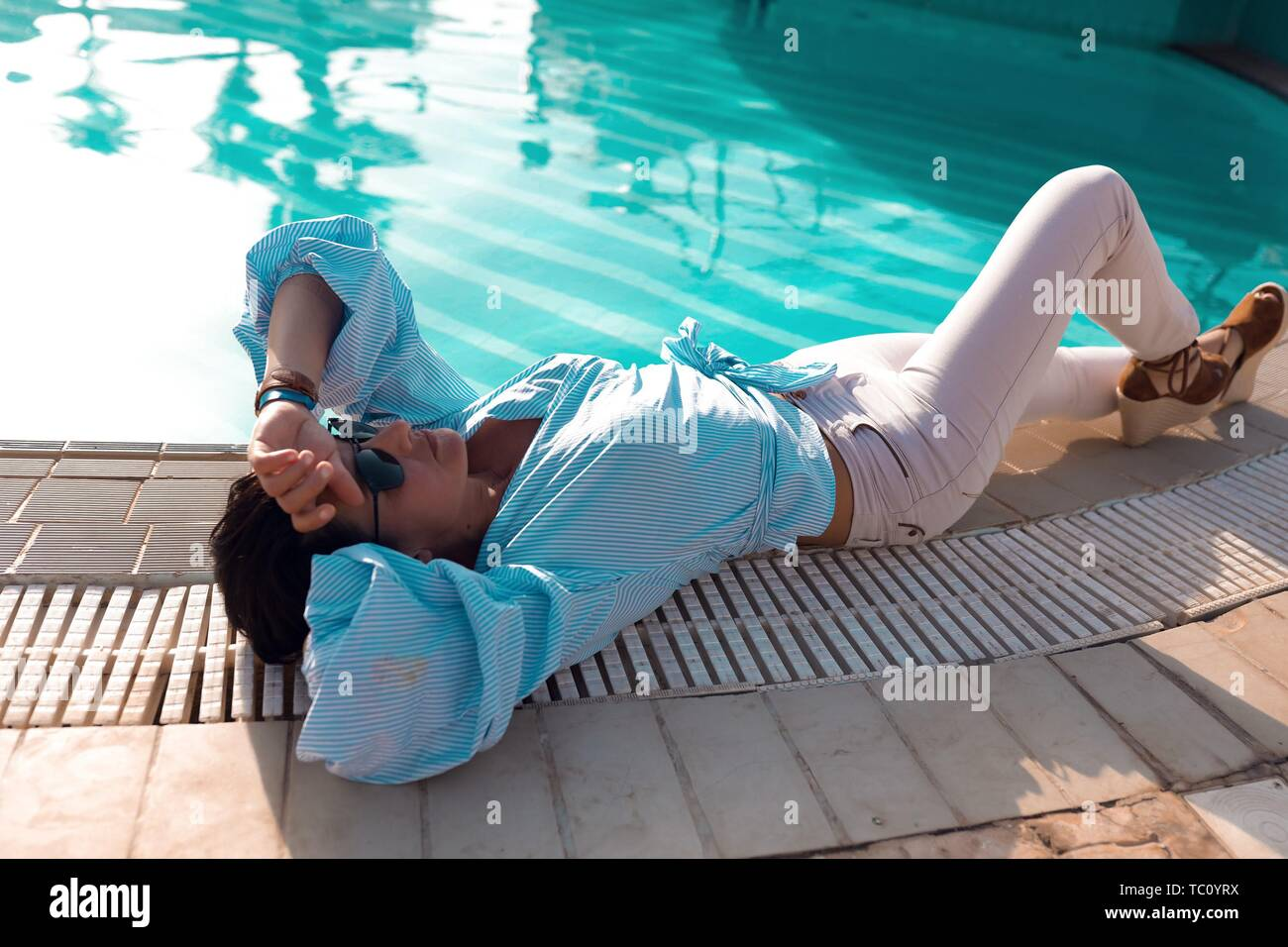 Slim young brunette relaxing outdoor near the pool with blue water. Lying on the floor, looking up to the sky. Wearing stylish white jeans and shirt Stock Photo