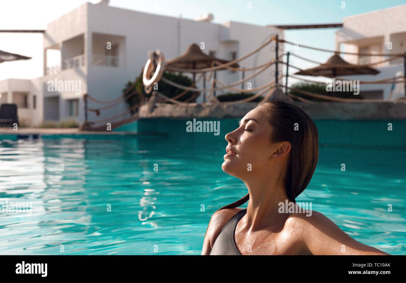 Close-up picture of young beautiful lady with long wet hair sitting in a pool outdoor, relaxing and taking sunbathes. Tender soft skin, slim body in Stock Photo