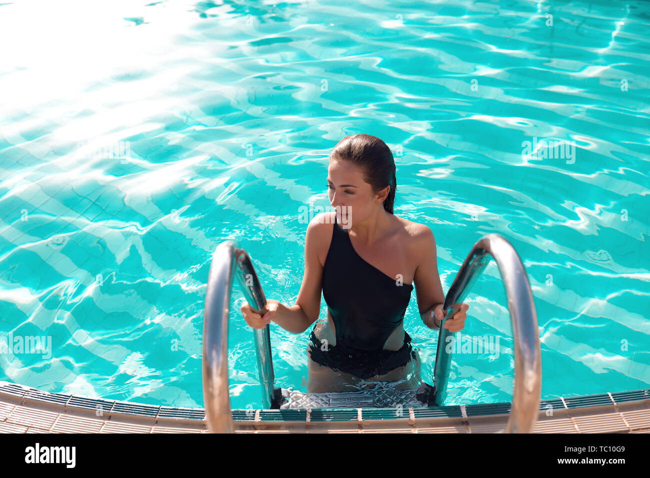 Tender young woman swimming in a pool with blue pure water, chilling out under burning sun.Modern black closed swimsuit, holding the stairs in a water Stock Photo