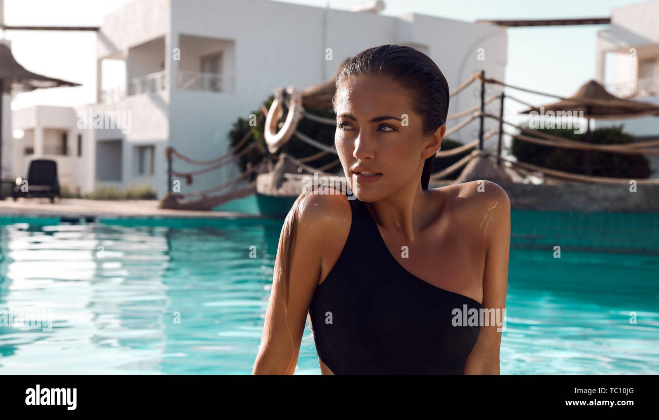 Beautiful face of young girl in a pool outdoor. Looking away and relaxing in cool water. Summer vacation in Egypt. Wearing black swimsuit with one sho Stock Photo