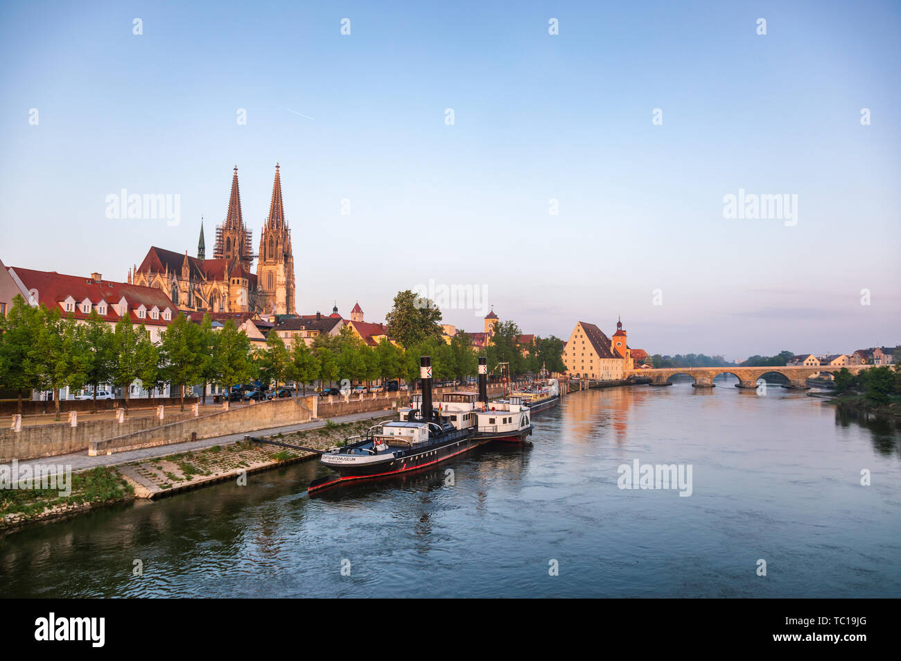 Regensburg cityscape as viewed from the Eiserne Brücke bridge with Donau-Schiffahrts-Museum on moored ships, St. Peter's Cathedral (Regensburger Dom)  Stock Photo