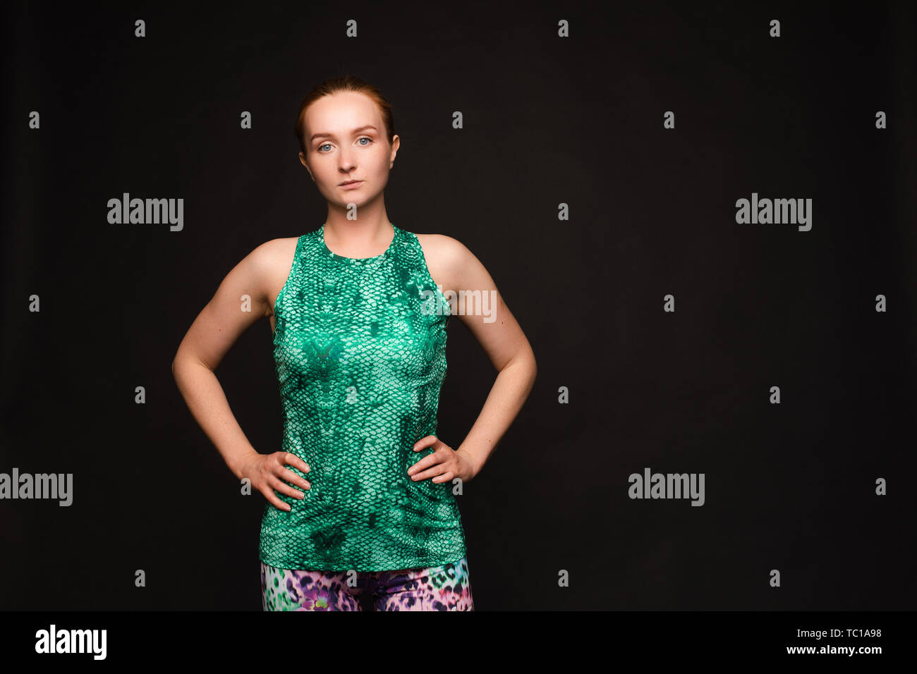 Strong red haired woman in sport uniform posing - Stock Image