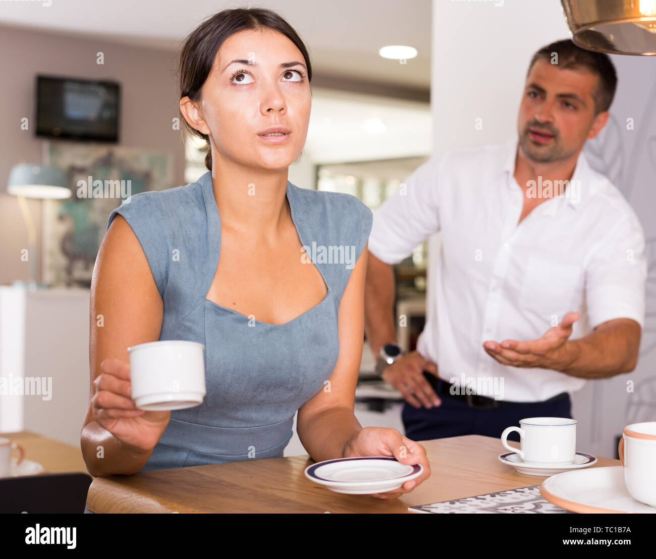 Upset young woman drinking tea at home table with disgruntled man behind her - Stock Image