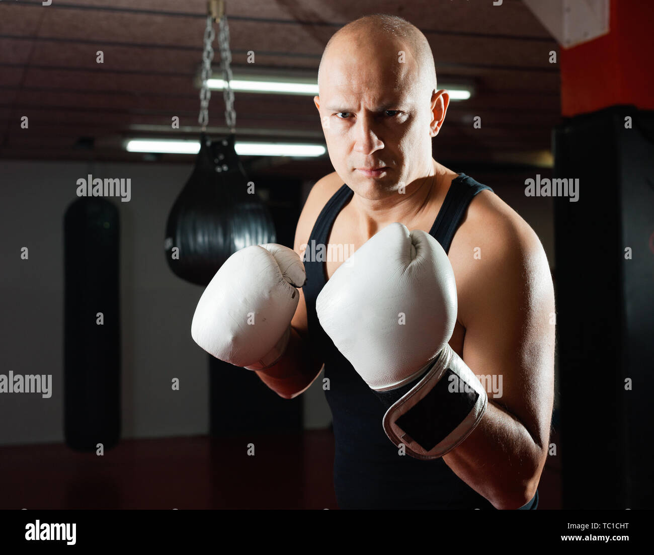 Potrait of  smiling man boxer who is training in gym - Stock Image