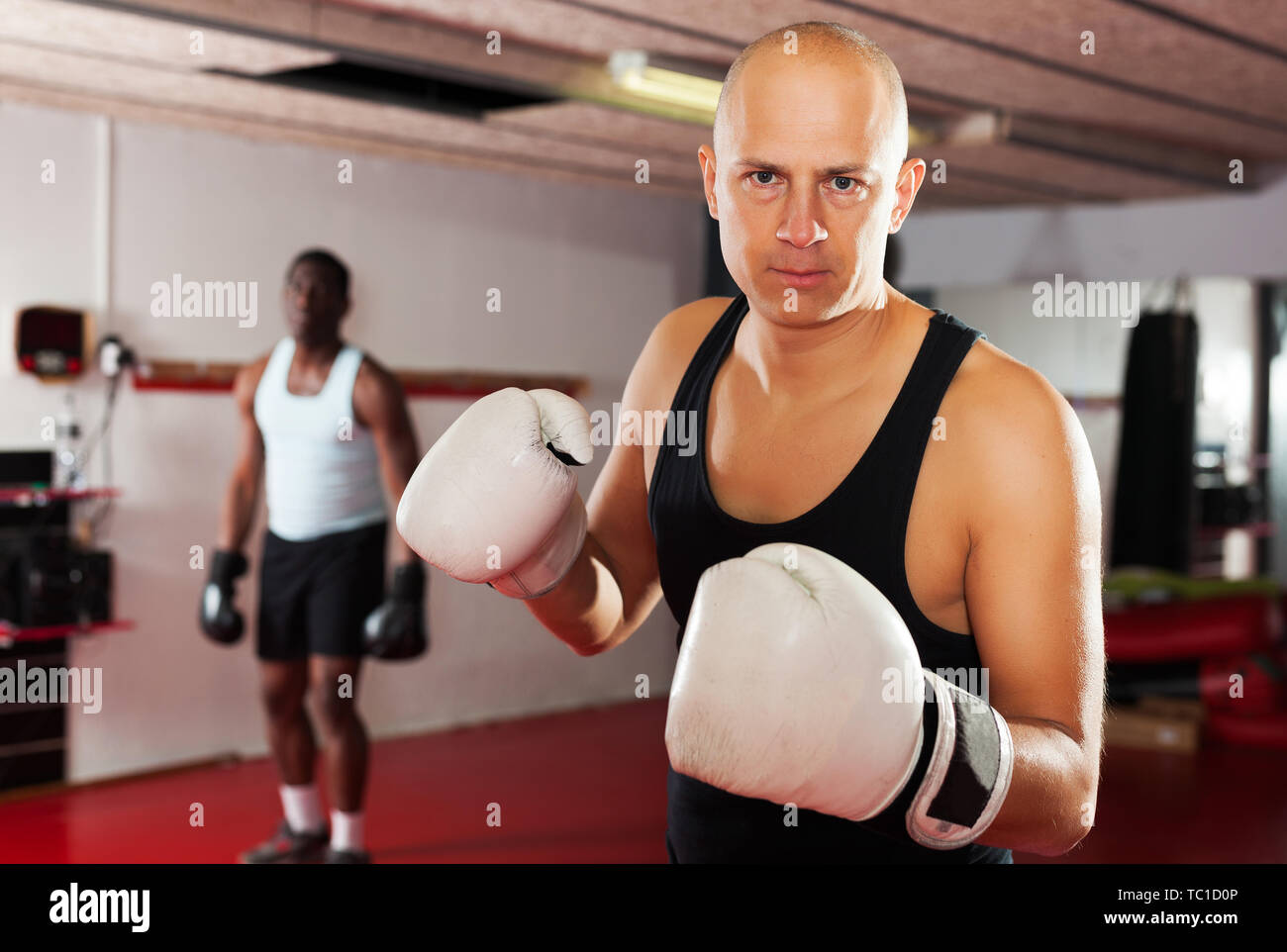 Potrait of serious man boxer who is training in gym - Stock Image