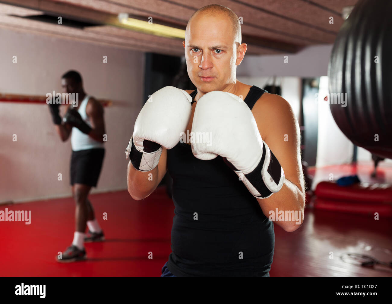 Potrait of active adut man boxer who is training in gym - Stock Image