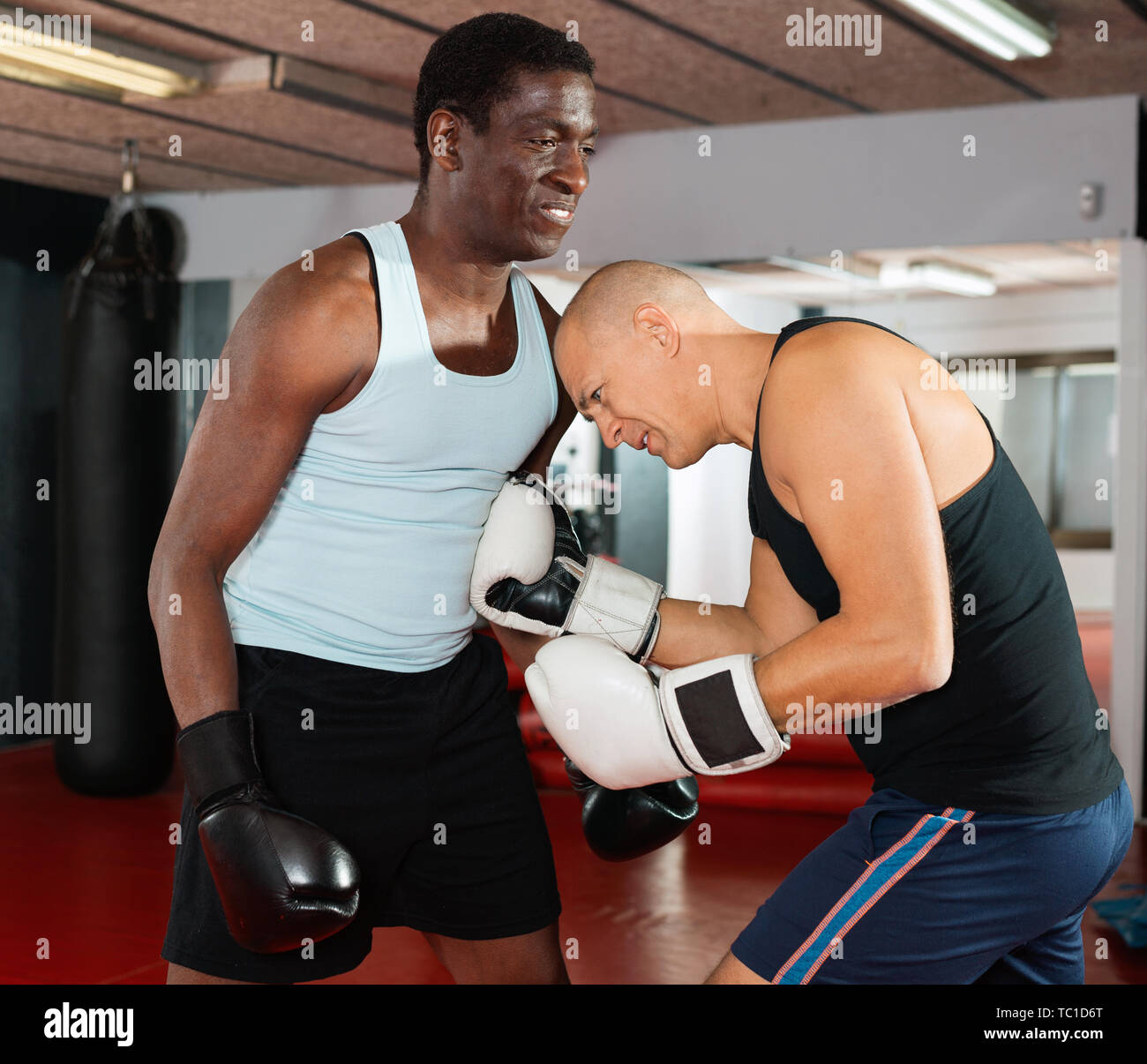 Two glad cheerful positive  athlete men in sportswear exercising boxing sparring in the hall - Stock Image