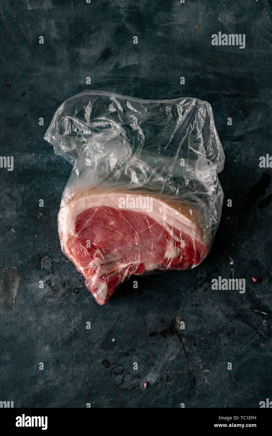 fresh bloody raw meat in a plastic bag straight after purchasing it at the butchers - Stock Image
