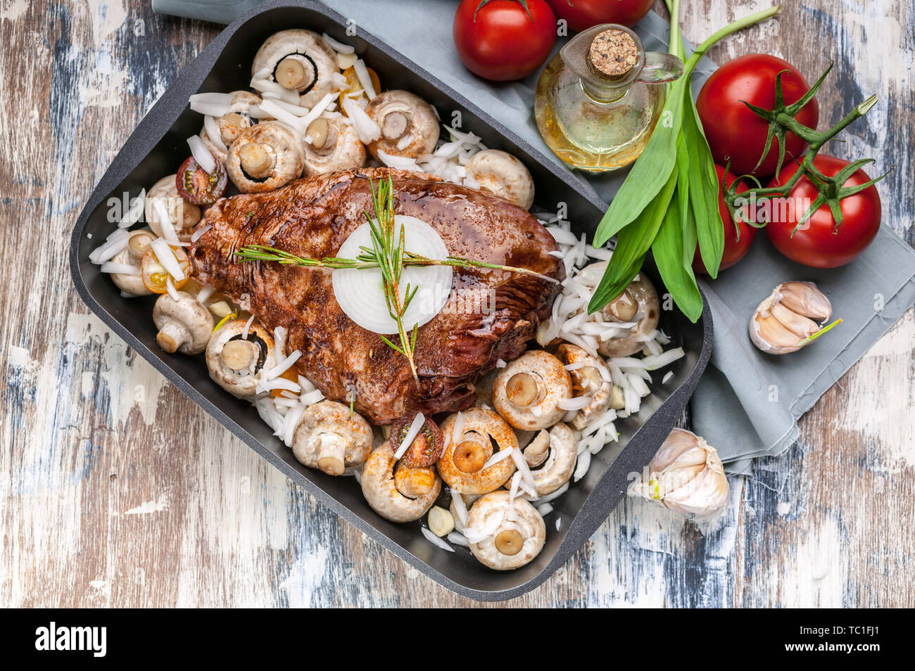 Marinated lamb with mushrooms, spices and herbs in a cast-iron mold on a wooden background. Tomatoes and olive oil. Halal meat and food. Top view - Stock Image