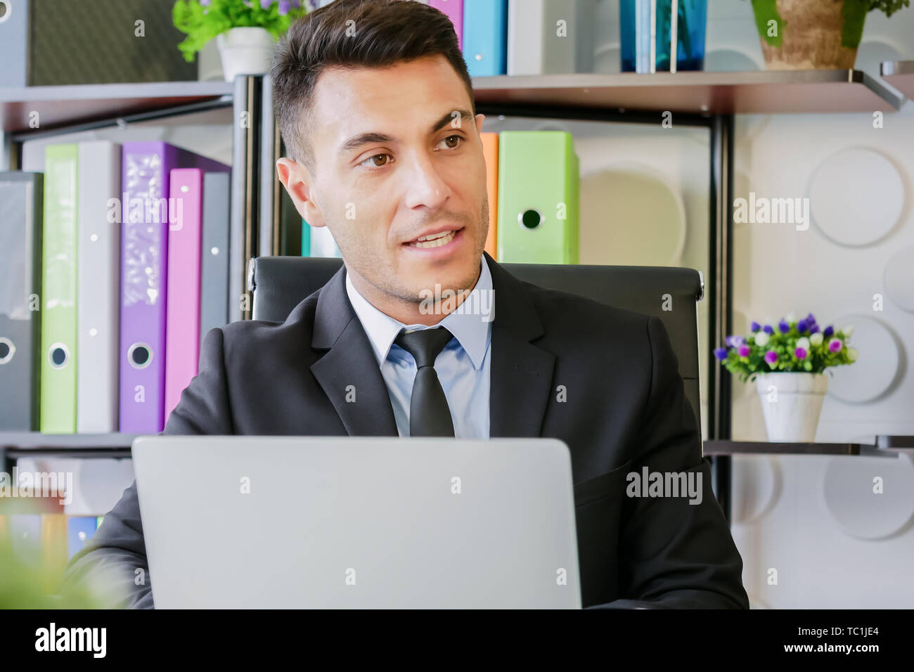 portrait business man work in modern office talking with laptop computer and talking to someone - Stock Image