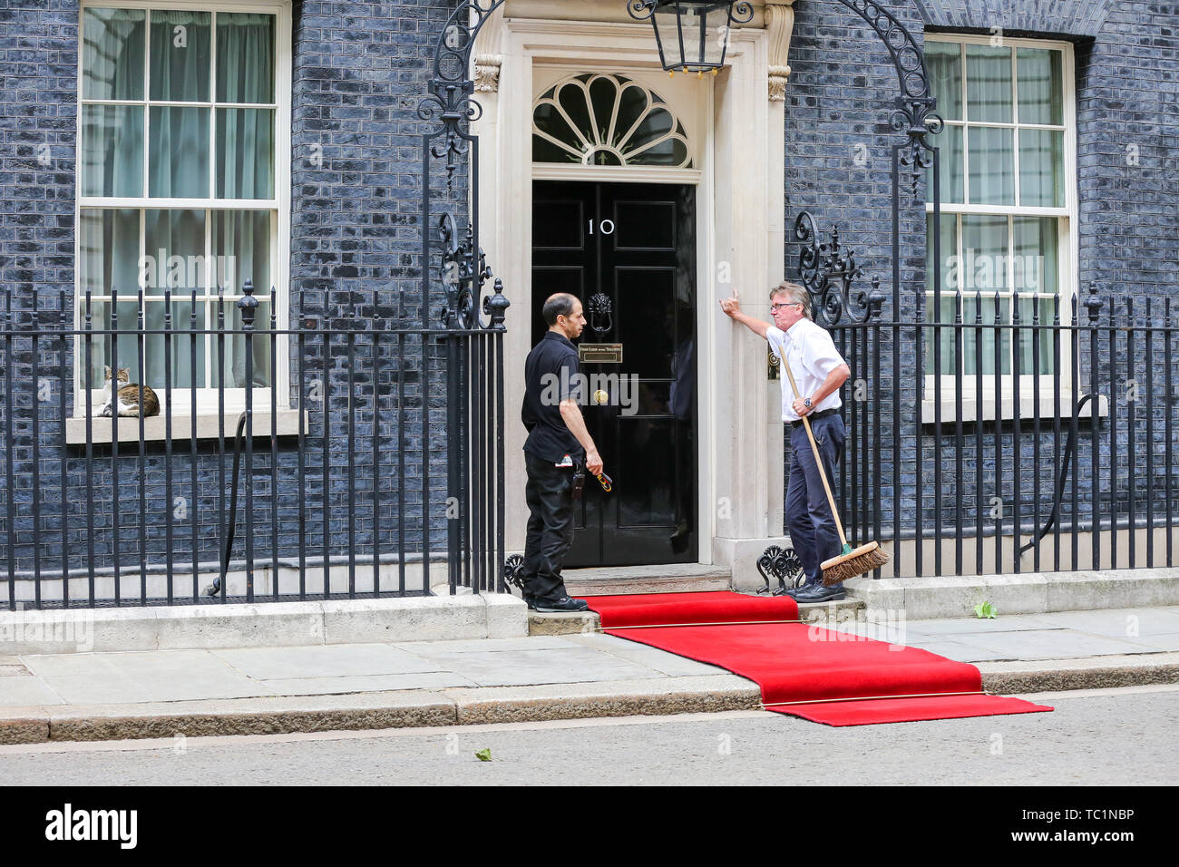 Workmen lay out a red carpet for the US President Donald