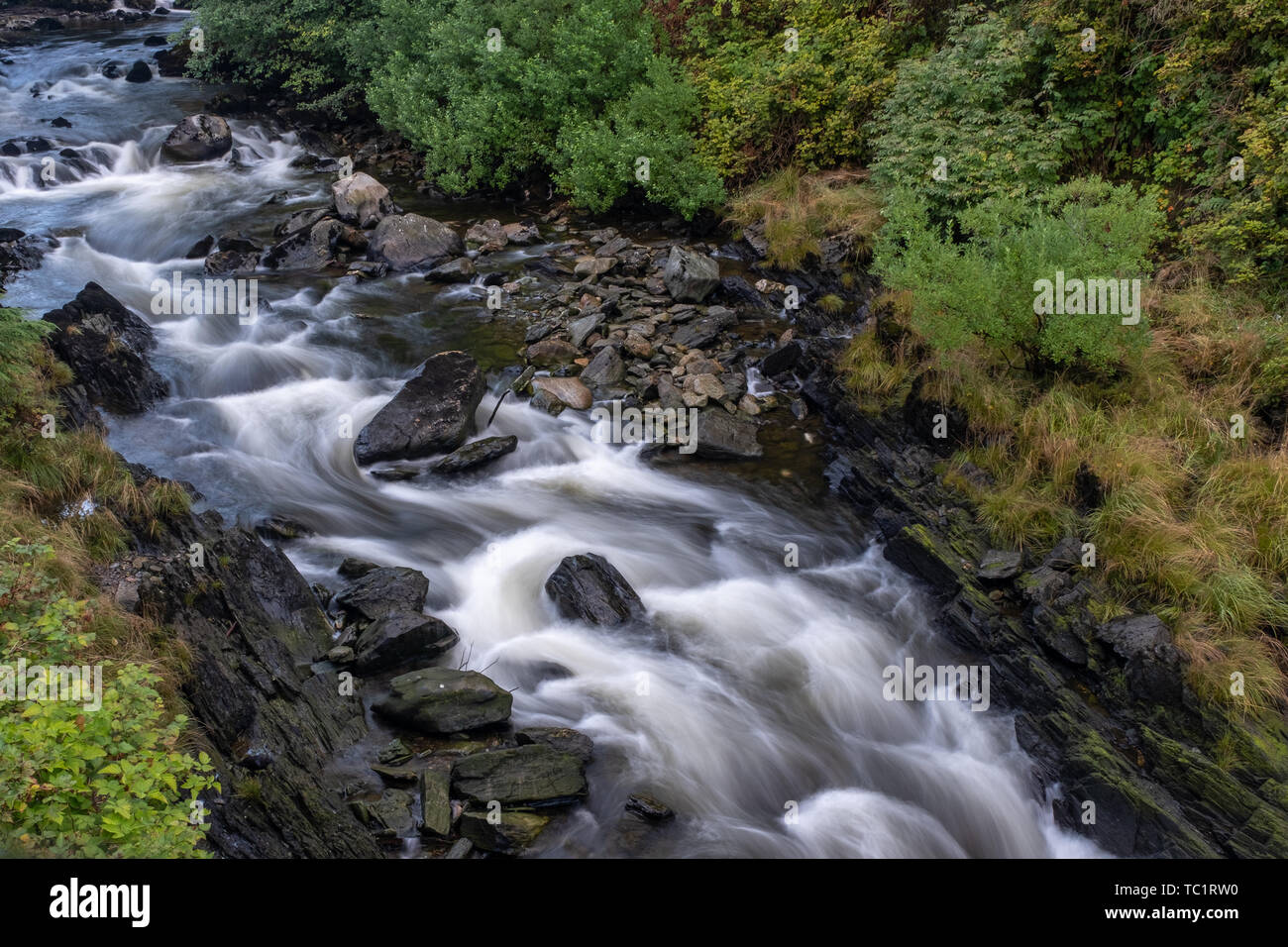 The bubbling Ketchikan Creek with a long exposure to create blurred motion to the water, close the famous Creek Street in Ketchikan, nobody in the ima - Stock Image