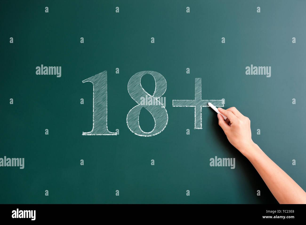 18 plus written on blackboard - Stock Image