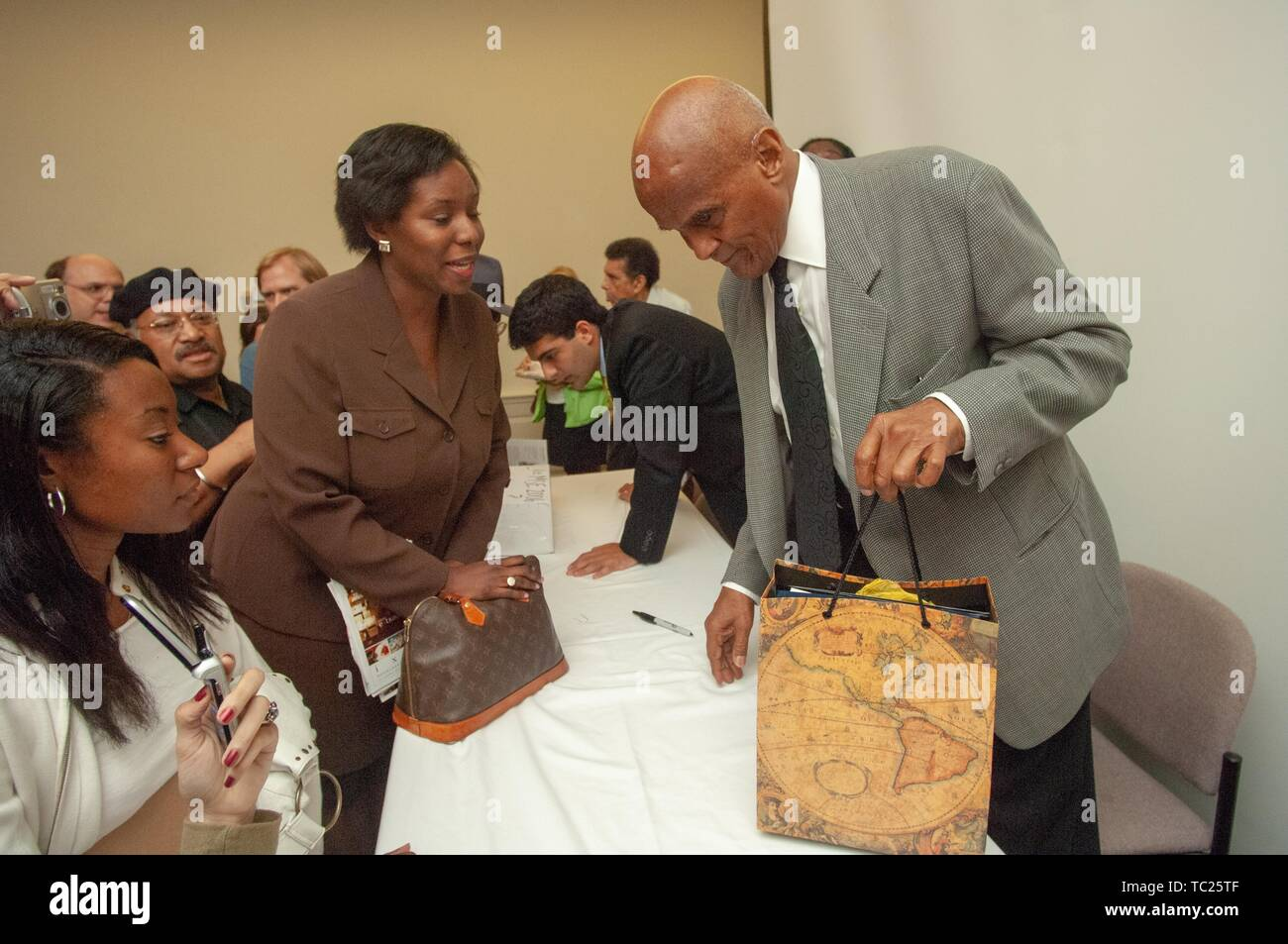 An attendee speaks with performer and activist Harry Belafonte during a Milton S Eisenhower Symposium, Homewood Campus of Johns Hopkins University, Baltimore, Maryland, September 19, 2006. From the Homewood Photography Collection. () Stock Photo