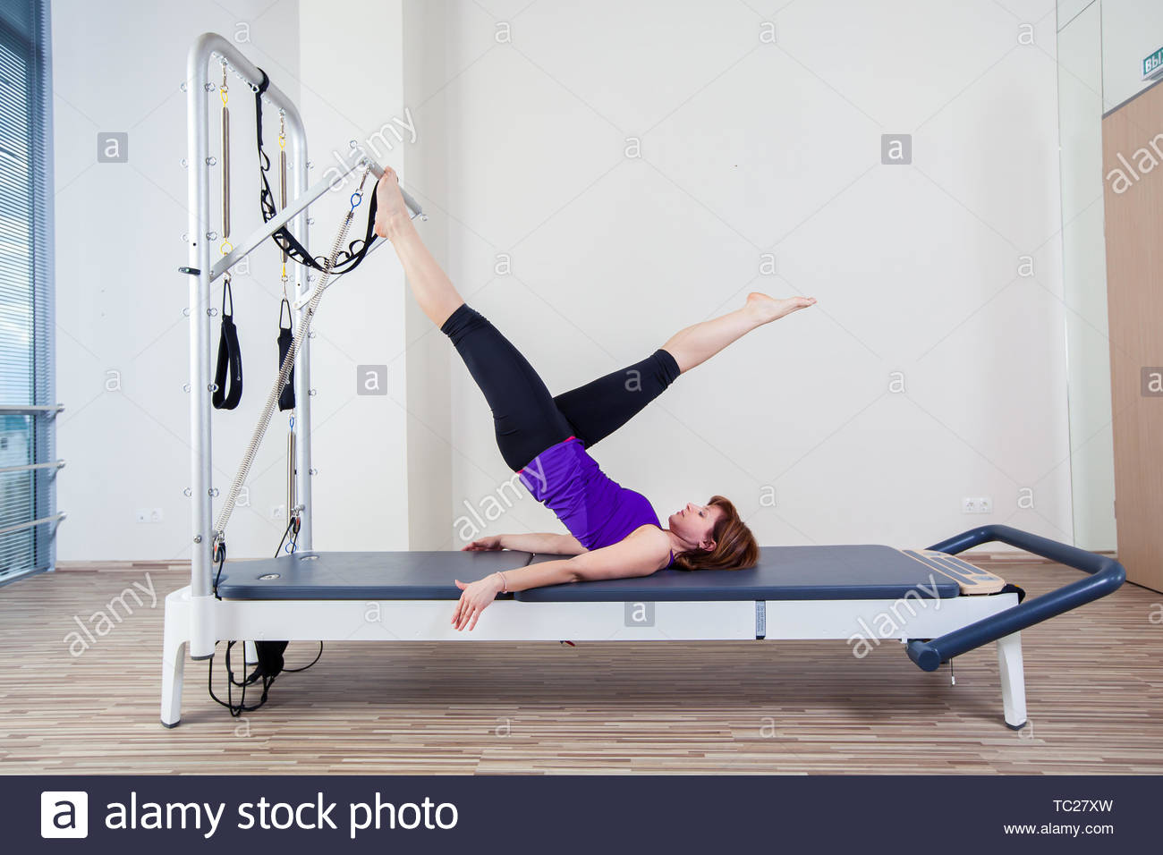 gym woman pilate instructor stretching in reformer bed. - Stock Image