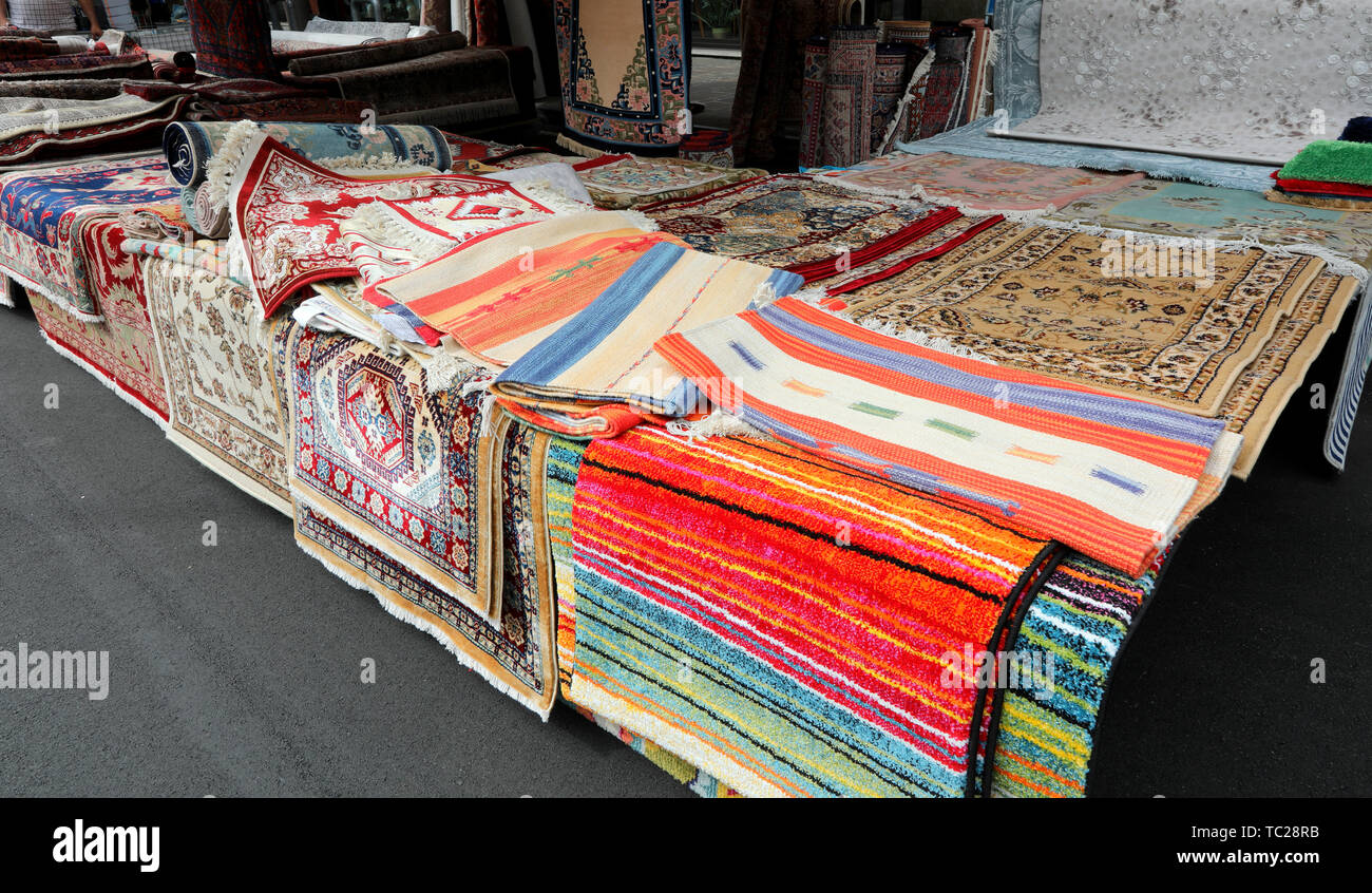 large market stall selling many oriental and kilim rugs - Stock Image