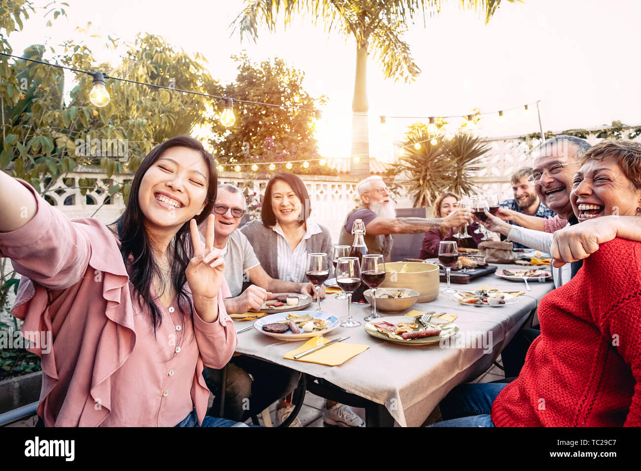 Happy family cheering and toasting with red wine glasses at dinner outdoor - People with different ages and ethnicity having fun at bbq party Stock Photo
