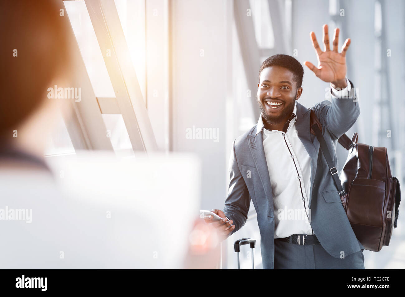 Hello! Businessman Waving To Partner Waiting For Him In Airport - Stock Image