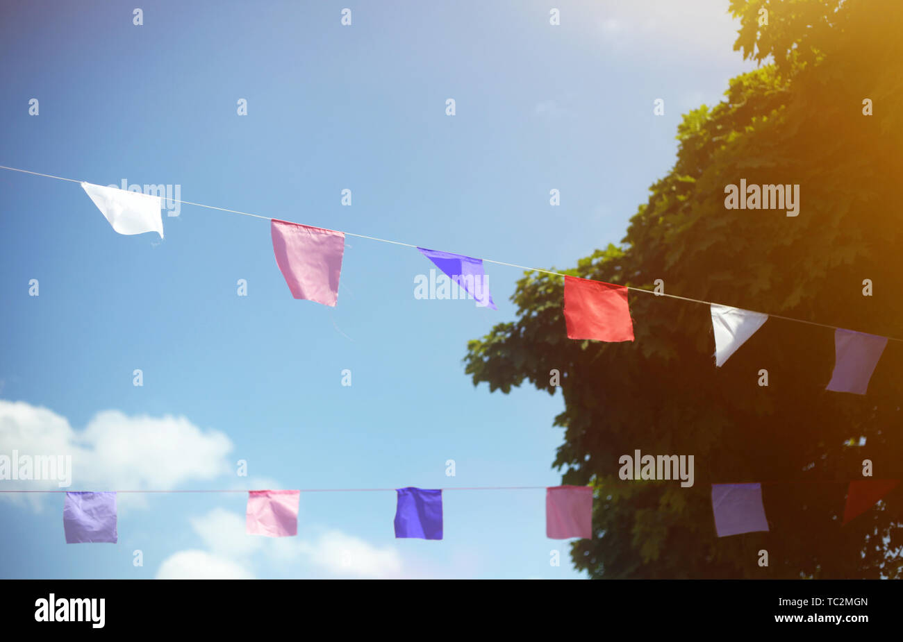 Colorful flags against blue sky with white clouds and trees. Summer street festival or party concept. - Stock Image