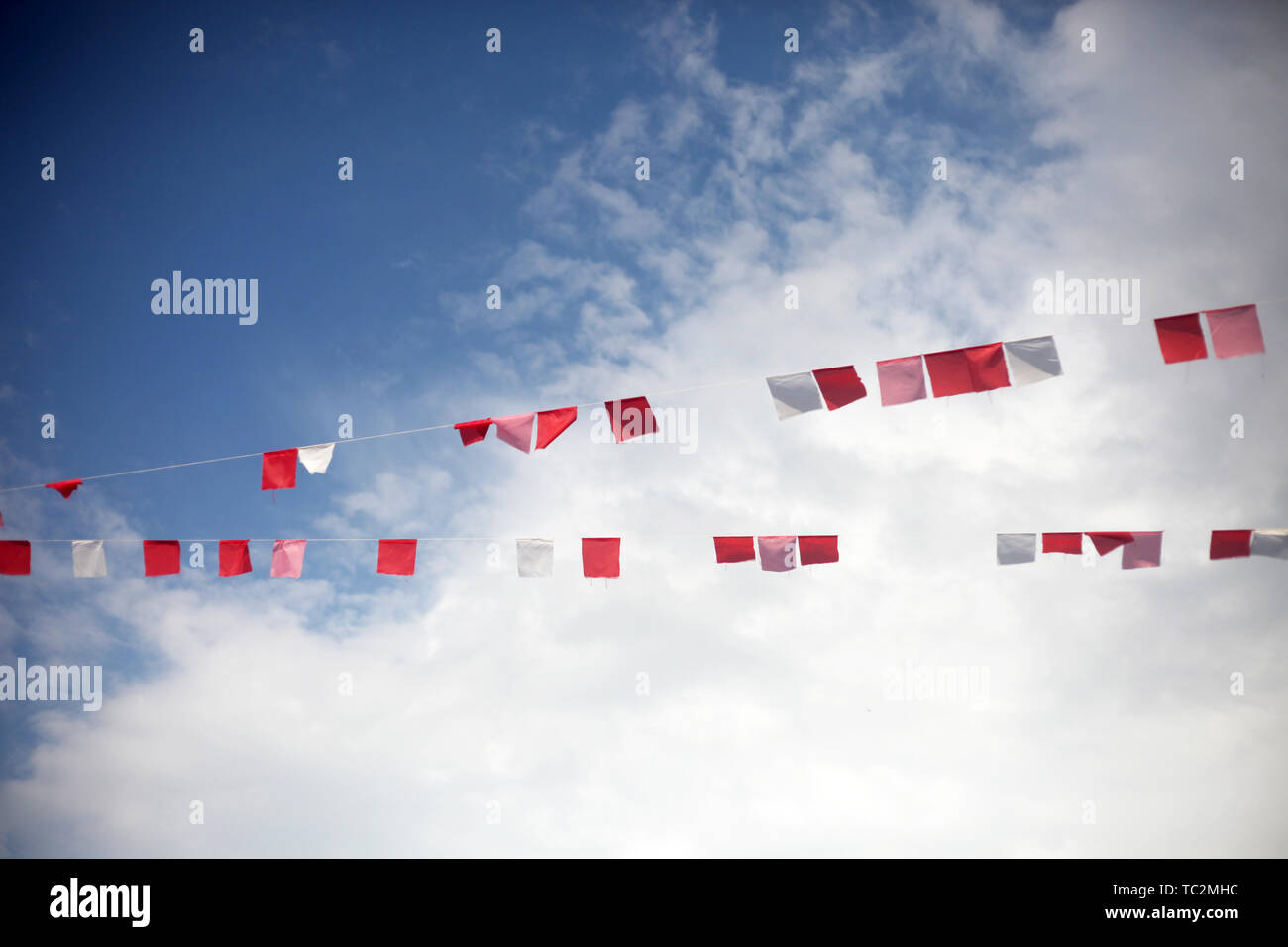 Colorful flags against blue sky with white clouds. Summer celebration, party or festival concept. - Stock Image
