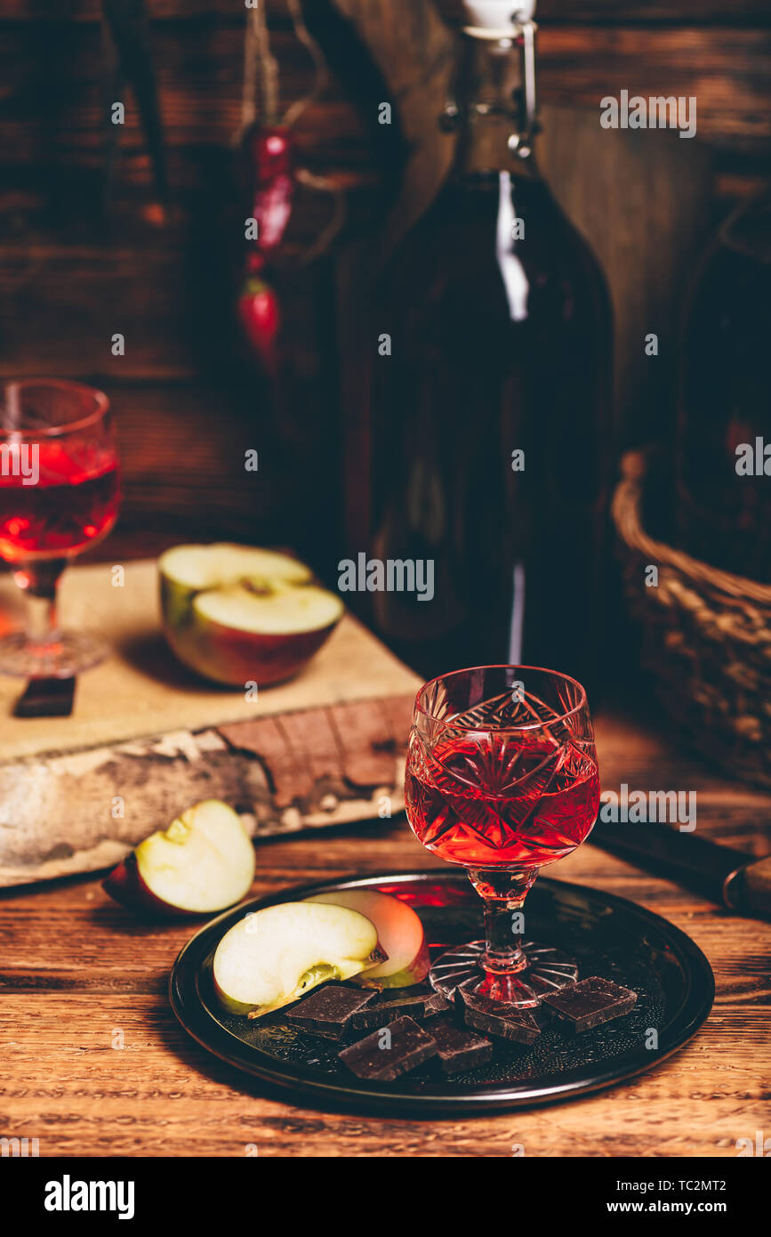 Homemade red currant nalivka and chocolate with sliced apple on metal tray - Stock Image