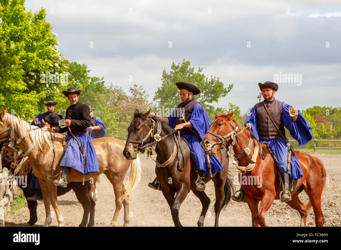 Kalocsa, Puszta, Hungary - May 23, 2019 : Hungarian Csikos horsemen displaying riding skills in traditional costume in countrside corral. Stock Photo