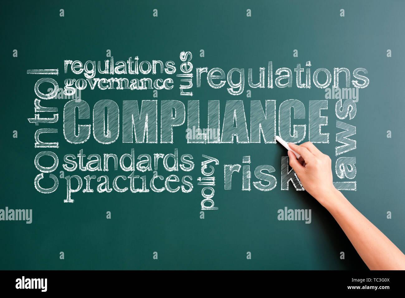 compliance written on blackboard - Stock Image