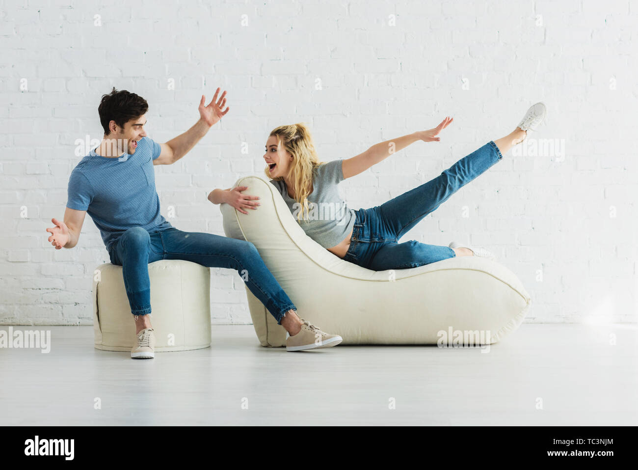 cheerful girl looking at man while gesturing and lying on bean bag chairs - Stock Image