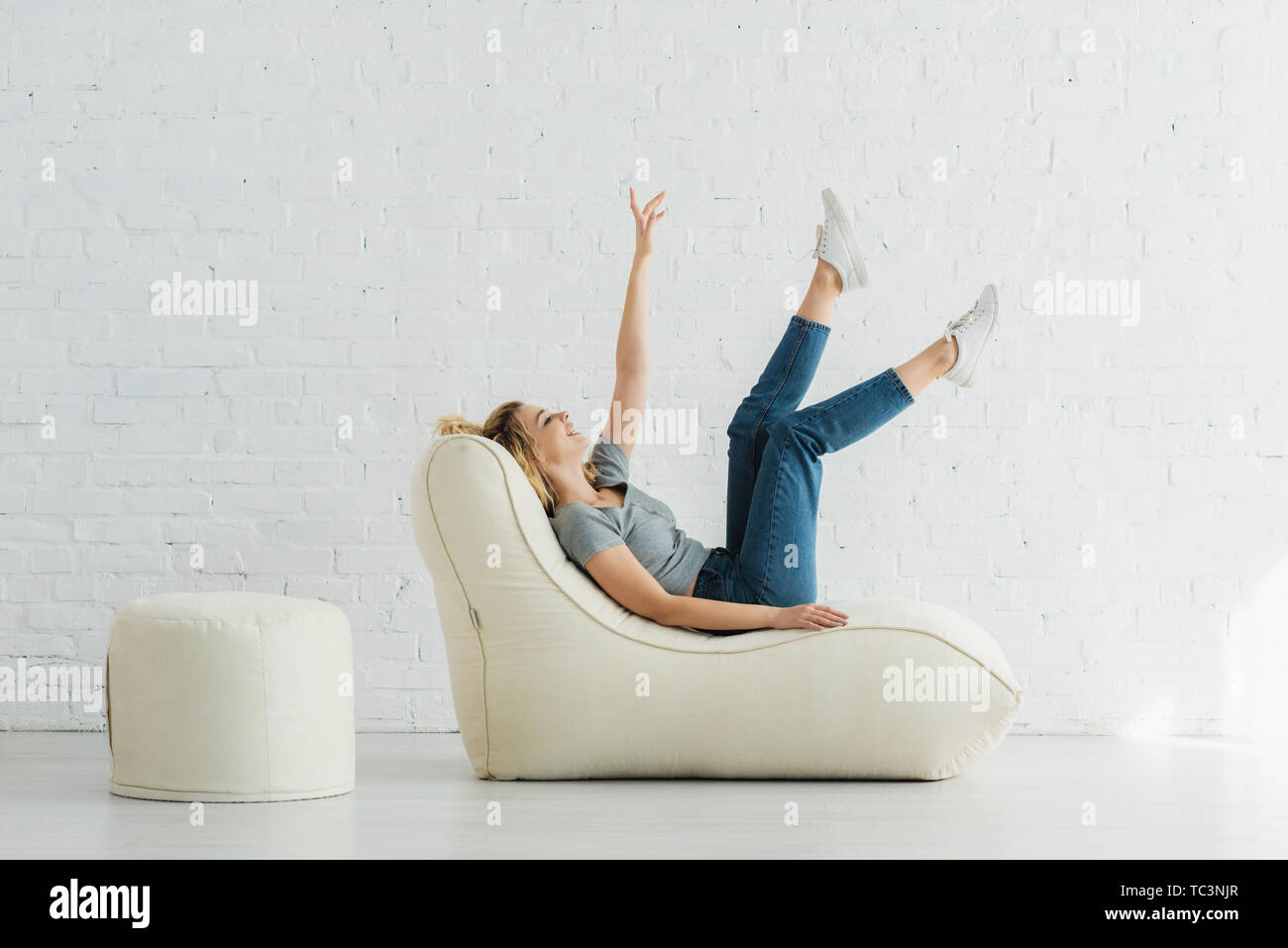 cheerful blonde girl lying on  bean bag chair and gesturing near brick wall - Stock Image