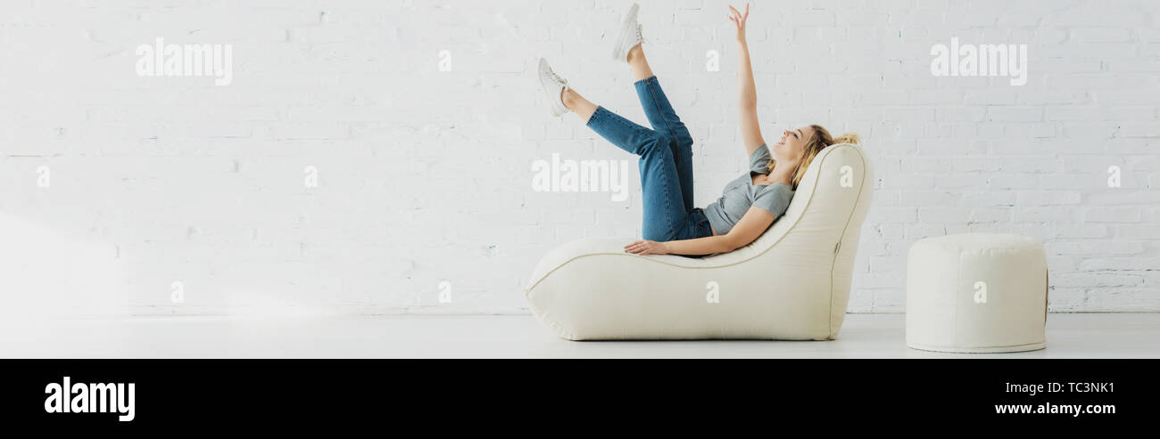 panoramic shot of cheerful blonde girl lying on  bean bag chair and gesturing near brick wall - Stock Image