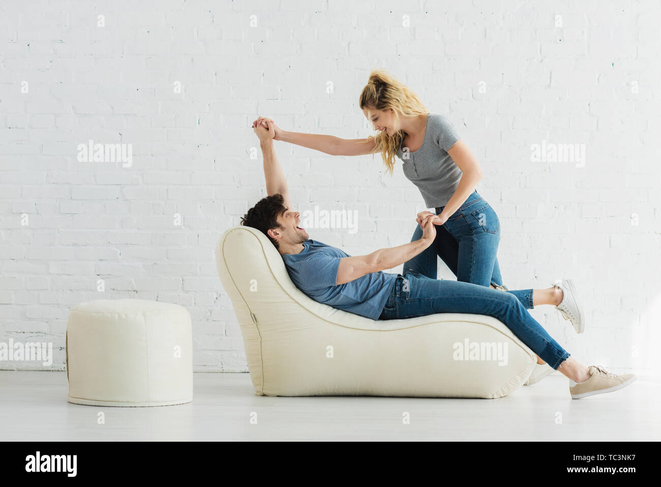 handsome man lying on bean bag chair and holding hands with blonde girl - Stock Image