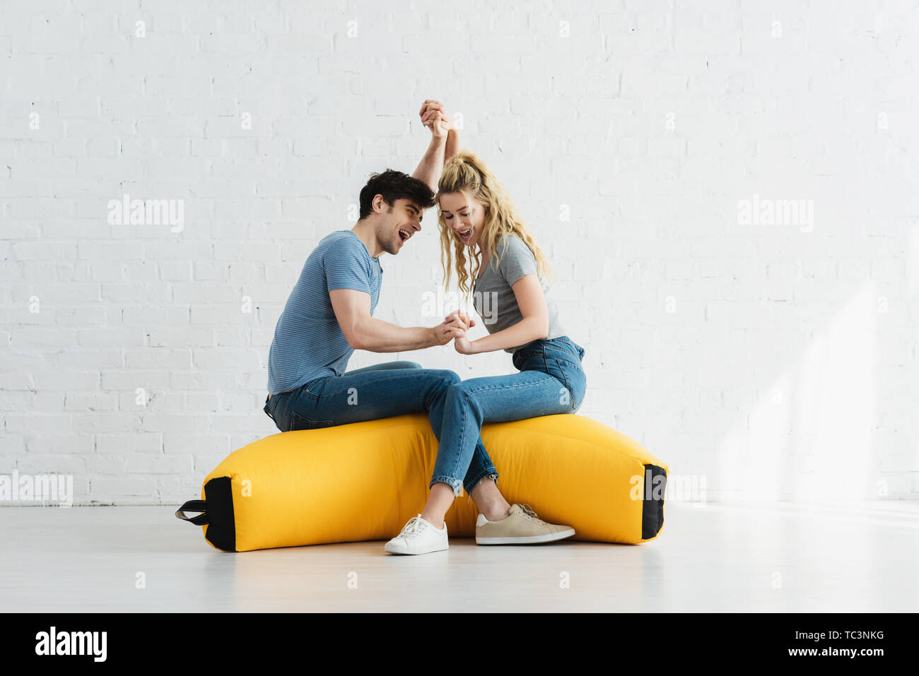 pretty blonde girl and handsome man holding hands while sitting on yellow bean bag chair - Stock Image