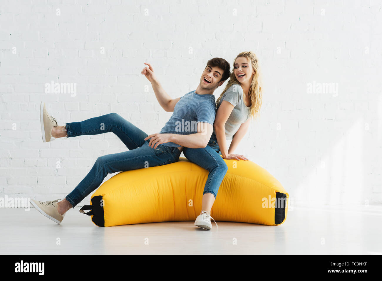 cheerful blonde girl and happy man sitting on yellow bean bag chair - Stock Image