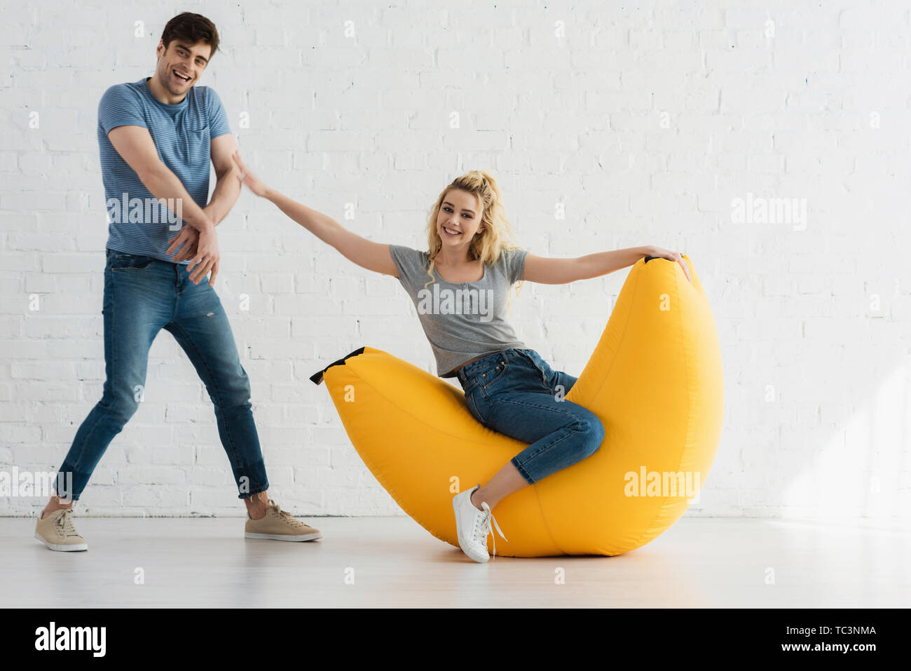 cheerful woman sitting on yellow bean bag chair and touching handsome man - Stock Image
