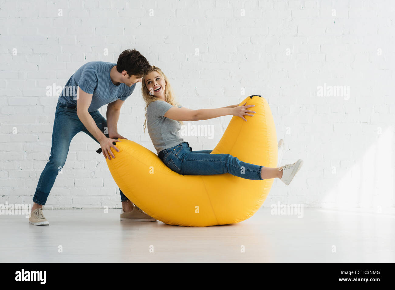 cheerful woman sitting on yellow bean bag chair and looking at handsome man - Stock Image