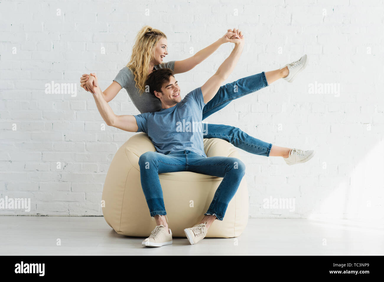 cheerful blonde girl and happy man holding hands while sitting on bean bag chair - Stock Image
