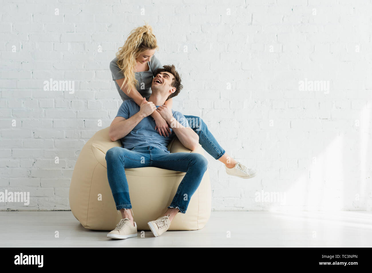 cheerful blonde girl hugging happy man sitting on beige bean bag chair at home - Stock Image