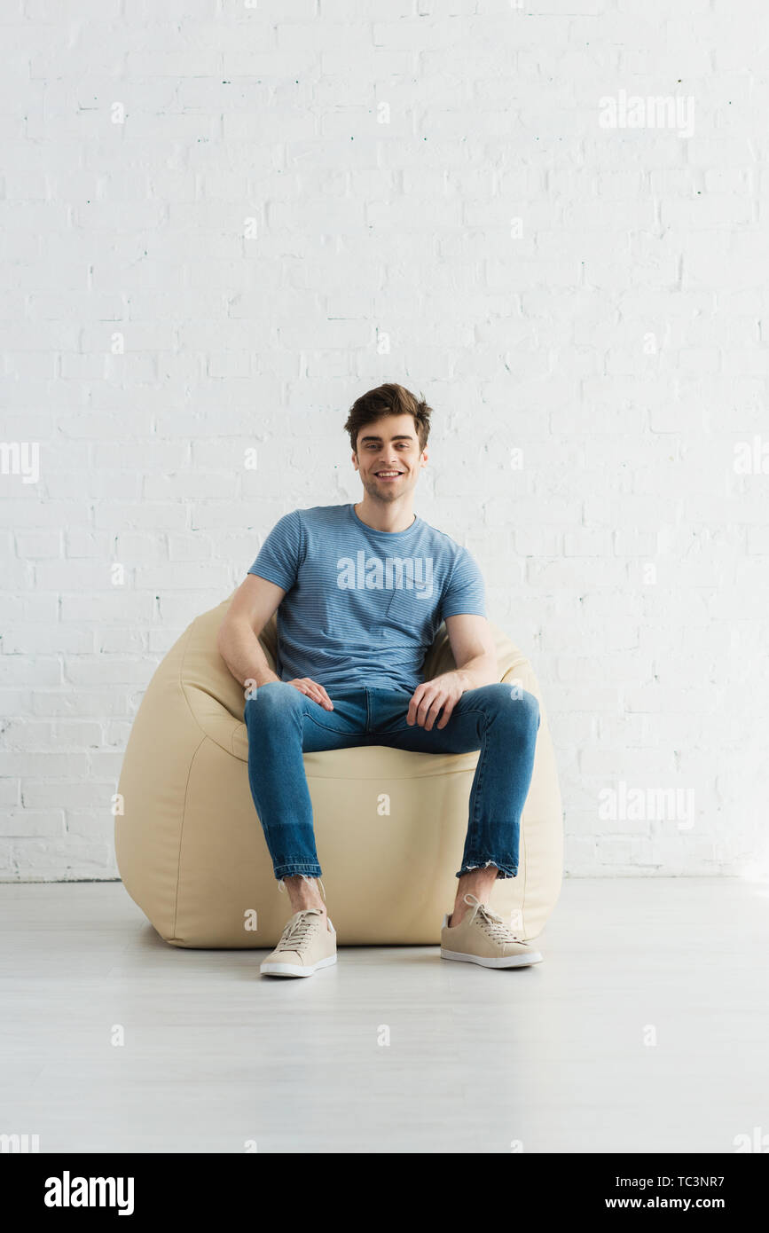happy and handsome man sitting on beige bean bag chair at home - Stock Image