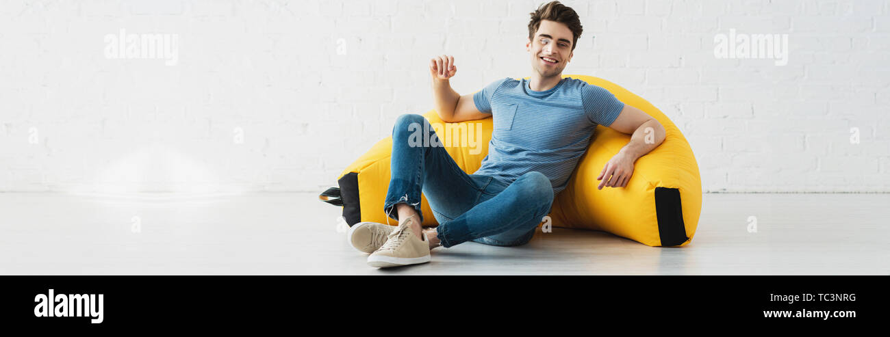panoramic shot of happy man sitting near yellow bean bag chair at home - Stock Image