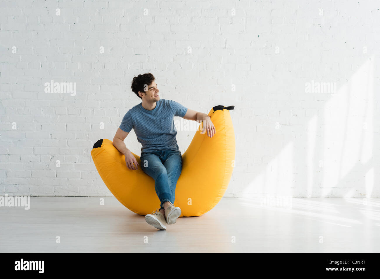 happy man sitting with crossed legs on yellow bean bag chair near white brick wall - Stock Image