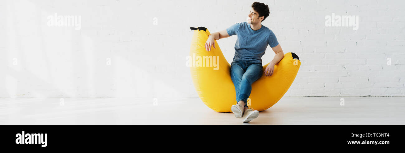 panoramic shot of happy man sitting on yellow bean bag chair at home - Stock Image
