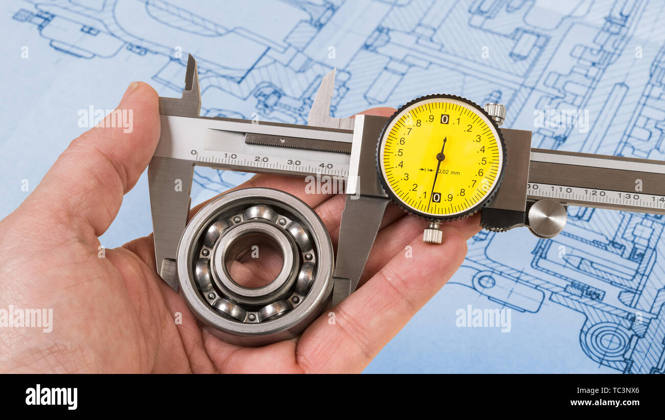 Ball bearing measurement. Vernier caliper in technician hand. Round steel part in jaws of metallic measuring tool with technical drawing on background. - Stock Image