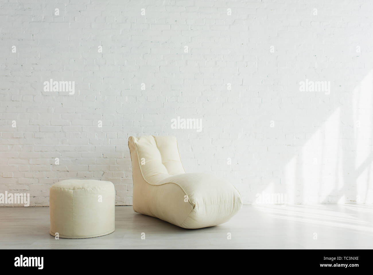 bean bag chair and pouf near white brick wall in modern home - Stock Image
