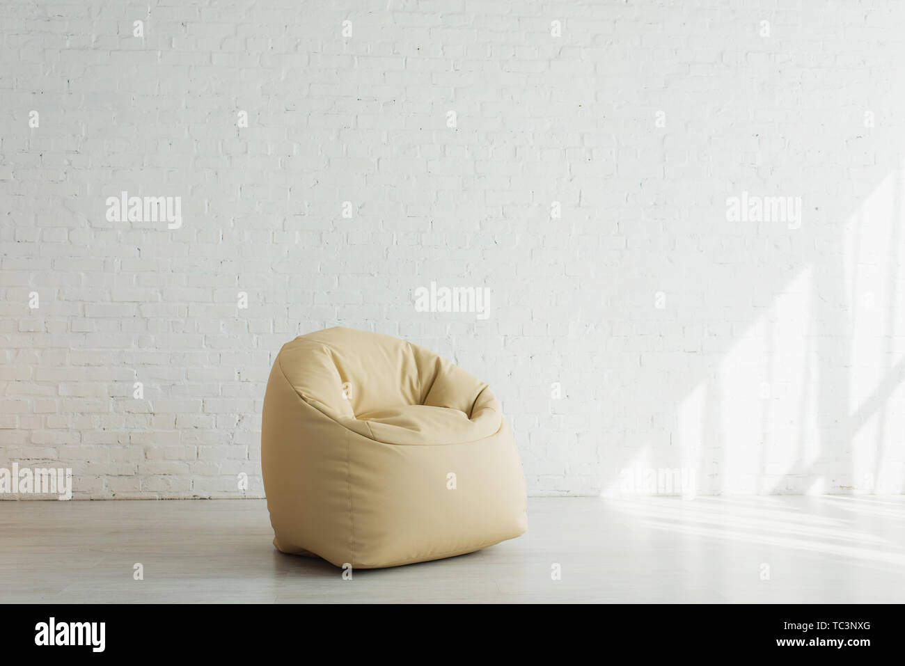 sunlight near beige bean bag chair near brick wall in modern home - Stock Image