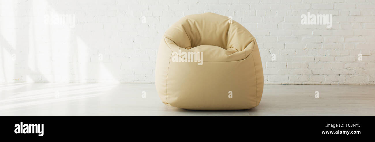 panoramic shot of bean bag chair near brick wall in modern home - Stock Image