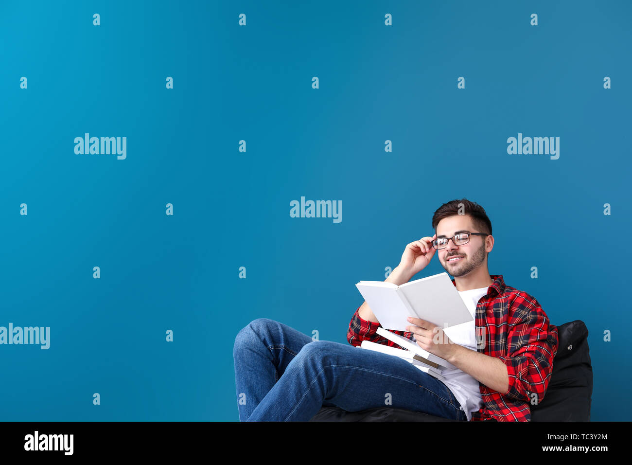 Handsome young man with books sitting near color wall - Stock Image
