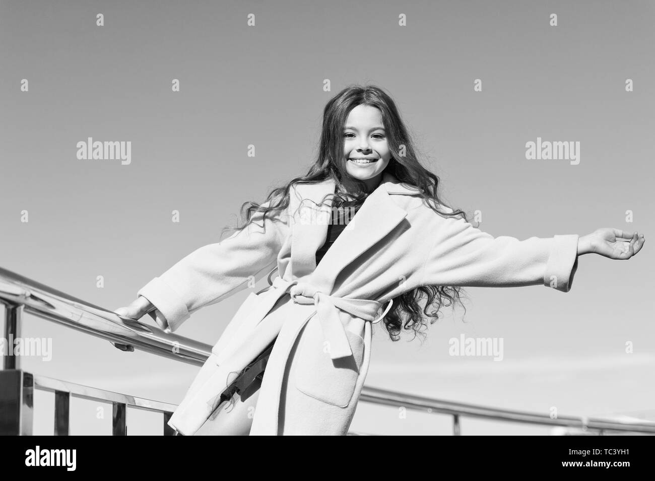 Kid girl long hair enjoy walk sunny day blue sky background. Girl carefree childhood walk. Charming little stylish fashionable girl. Feeling free and happy. Little child enjoy sunny walk. Happy day. Stock Photo