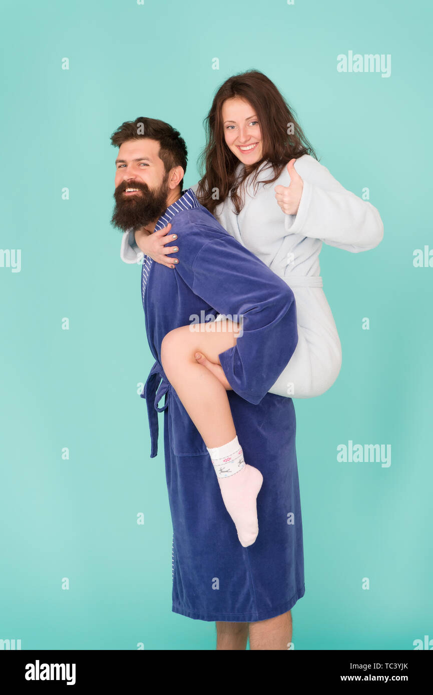 Trust and support. True love. Lets stay at home. They are closest people. Support in any time. Reliable support. Handsome young man piggybacking beautiful woman. Couple in bathrobes having fun. - Stock Image